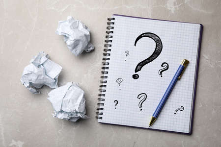 Notebook with question marks, pen and crumpled paper balls on grey marble table, flat lay