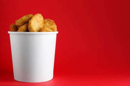 Bucket with delicious chicken nuggets on red background. Space for text