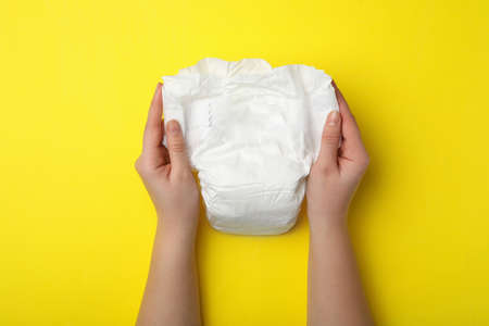 Woman with diaper on yellow background, closeup Stock Photo