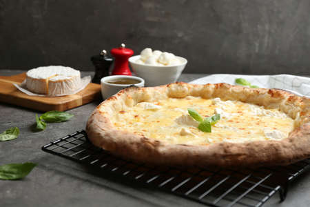 Delicious hot cheese pizza on grey table