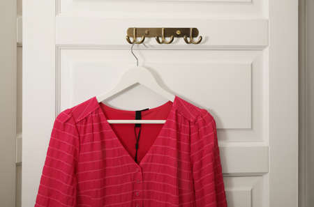 Hanger with beautiful blouse on white door
