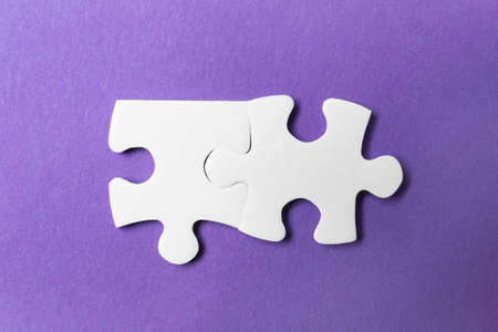 Unfitting white puzzle pieces on purple background, flat lay