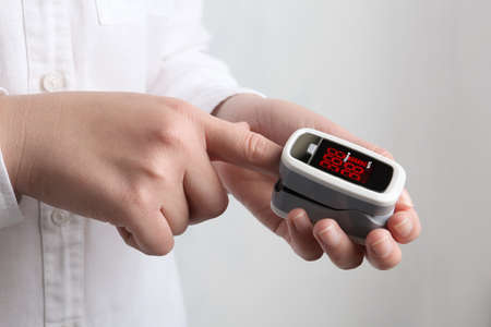 Woman using modern fingertip pulse oximeter on light background, closeup