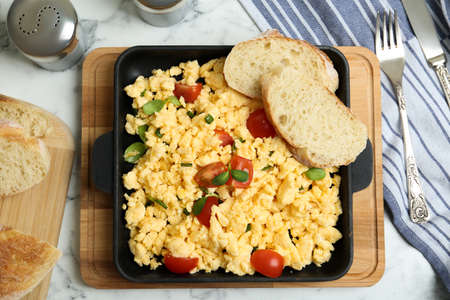 Tasty scrambled eggs served on white marble table, flat lay