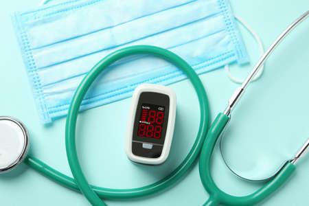 Modern fingertip pulse oximeter, mask and stethoscope on light blue background, flat lay Foto de archivo