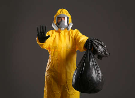 Woman in chemical protective suit holding trash bag on grey background. Virus research