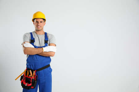Carpenter with tool belt on light background. Space for text