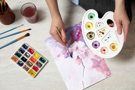 Woman painting flowers with watercolor on floor, top view