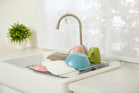 Drying rack with clean dishes over sink in kitchen