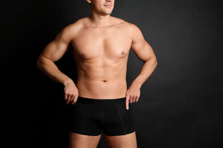 Man with muscular body on black background, closeup. Space for text