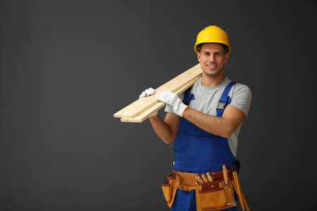 Handsome carpenter with wooden planks on dark background Фото со стока