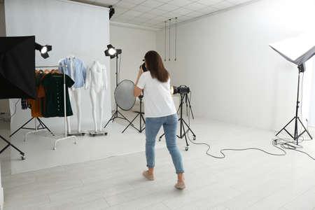 Professioneller Fotograf, der Geisterpuppen mit moderner Kleidung im Fotostudio fotografiert