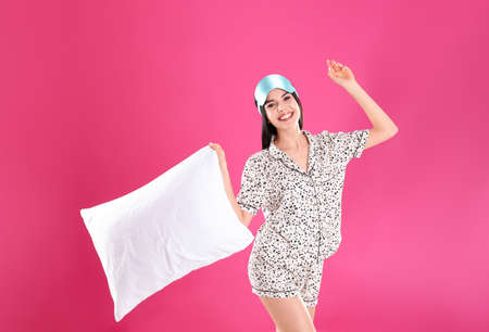 Young woman with pillow and sleep mask on pink background Stockfoto