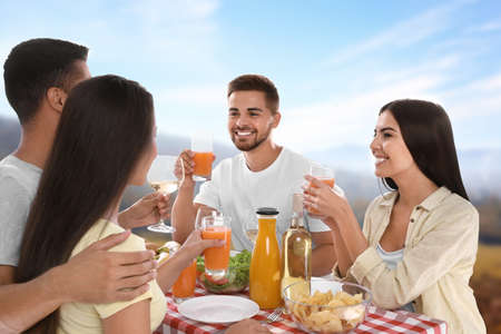 Group of friends having picnic at table in park
