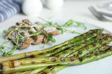 Tasty meat served with grilled asparagus on plate, closeup