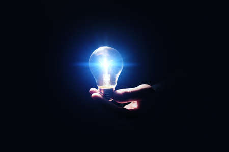 Idea concept. Man with glowing light bulb in darkness, closeup
