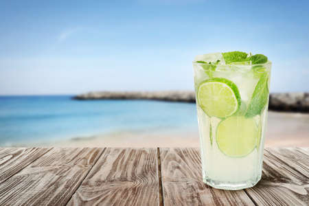 Tasty lemonade with ice cubes and lime on wooden table near sea, space for text 版權商用圖片 - 147717200