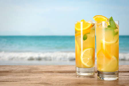 Glasses of refreshing lemonade on wooden table near sea, space for text 版權商用圖片 - 147717918