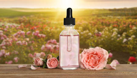 Bottle of rose essential oil and flowers on wooden table against blurred background Standard-Bild