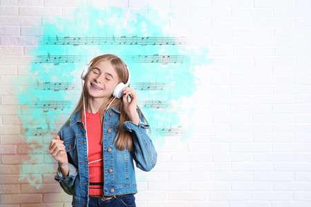 Teen girl listening music with headphones near brick wall