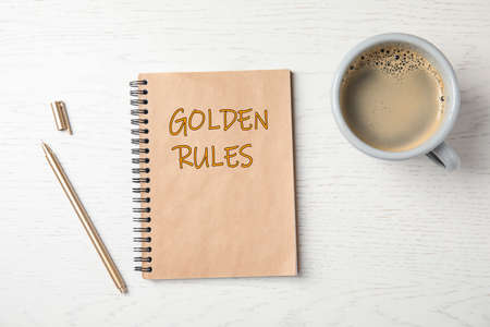 Notebook with phrase GOLDEN RULES and cup of coffee on wooden background, top view
