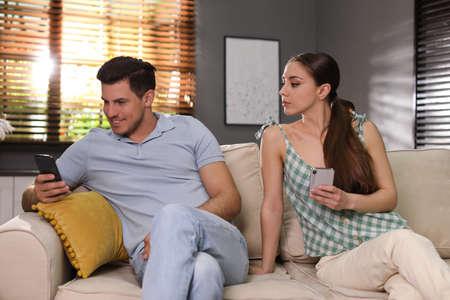 Distrustful woman peering into boyfriend's smartphone at home. Jealousy in relationship Foto de archivo