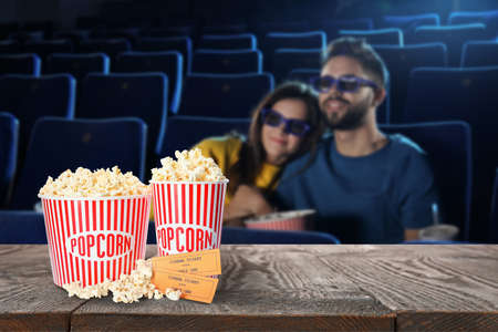 Popcorn, tickets on table and young couple in cinema hall