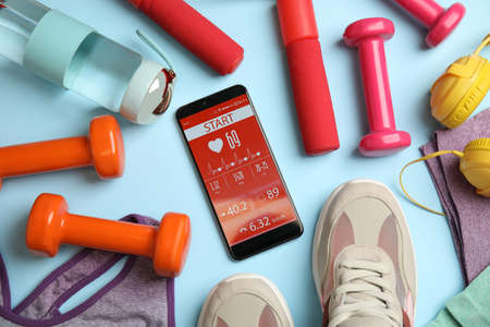Flat lay composition with fitness equipment and smartphone on light blue background Фото со стока
