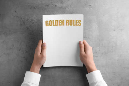 Man holding booklet with phrase GOLDEN RULES at grey table, top view