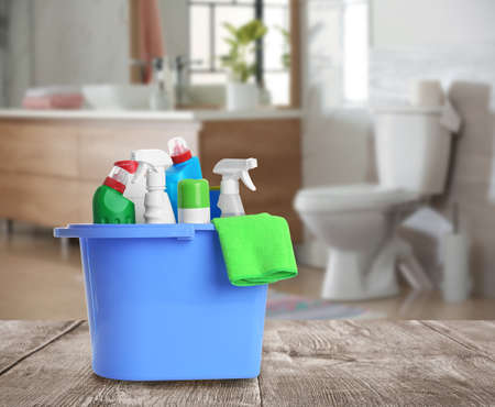 Bucket with cleaning supplies on wooden table in bathroom