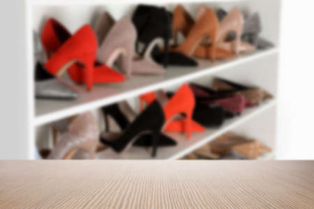 Empty wooden surface and blurred view of shelving unit with shoes in store, space for text Banco de Imagens