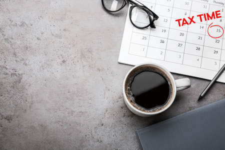 Calendar with words TAX TIME and cup of coffee on grey table, flat lay. Space for text Banque d'images