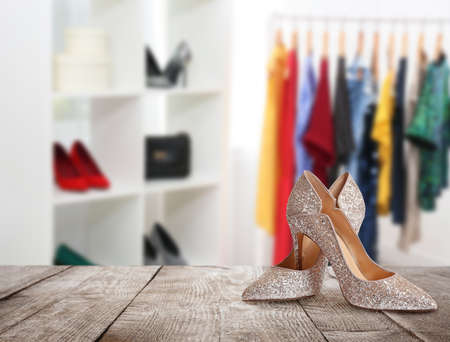 Stylish high heel shoes on wooden surface in store, space for text