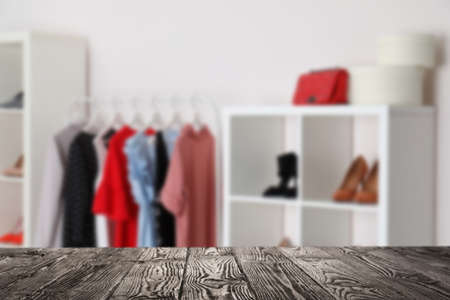 Empty wooden surface and blurred view of shoes store, space for text
