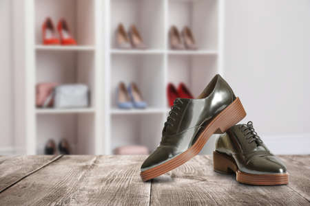Elegant shoes on wooden surface in store, space for text Imagens