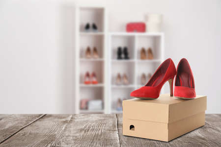 Pair of stylish high heel shoes and carton box on wooden surface in store, space for text Imagens