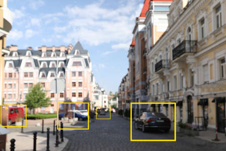 Blurred view of buildings and street with scanner frames on cars in city. Machine learning