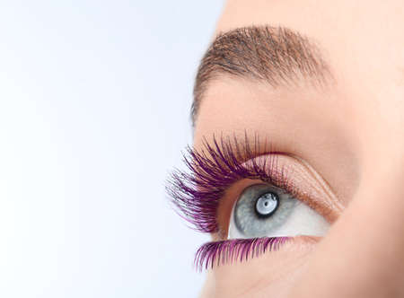 Young woman with beautiful purple eyelashes on light background, closeup. Space for text