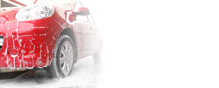 Red auto with foam at car wash, space for text. Banner design Zdjęcie Seryjne