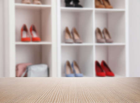 Empty wooden surface and blurred view of shelving unit with shoes in store, space for text Imagens