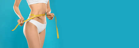 Closeup view of slim woman in underwear with measuring tape on color background, space for text. Banner design