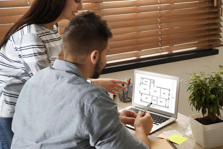 Architects making project of house on laptop in office