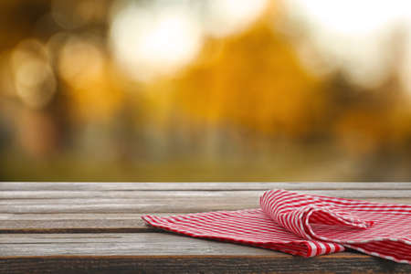 Picnic wooden table with checkered red napkin outdoors Stock Photo