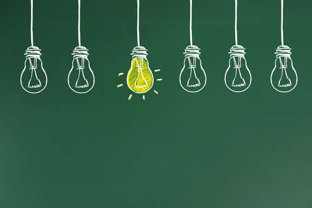Idea concept. Light bulbs drawn on green chalkboard 版權商用圖片