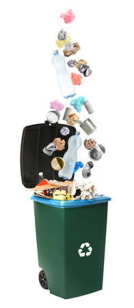 Different garbage falling into trash bin. Waste management and recycling