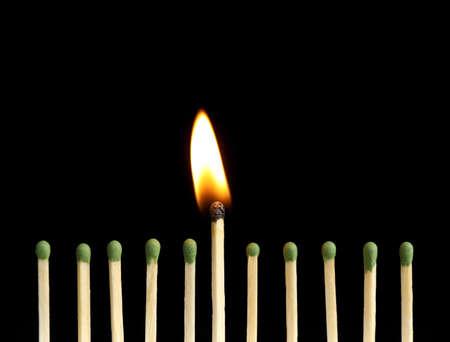 Burning match among unlit ones on black background, closeup
