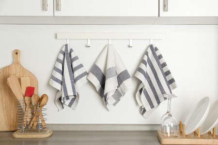 Different kitchen towels hanging on hook rack indoors