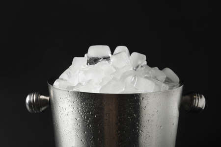 Metal bucket with ice cubes on dark background, closeup Reklamní fotografie