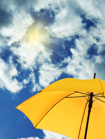 Modern yellow umbrella against blue sky, space for text. Sun protection Фото со стока