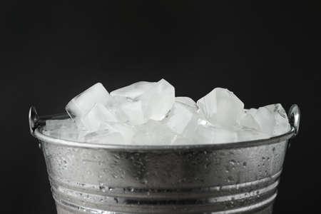 Metal bucket with ice cubes on dark background, closeup Reklamní fotografie
